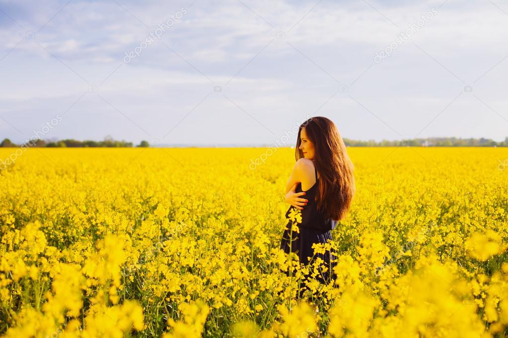 Girl hugs herself on rapeseed meadow