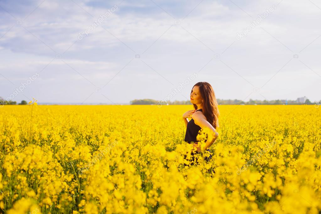Girl touches her shoulder on rapeseed meadow