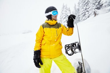 Close up portrait of male snowboarder wearing helmet with glasses, yellow jacket and pants, black gloves standing with snowboard in one hand and planning freeride route against blizzard - extreme sports concept stock vector