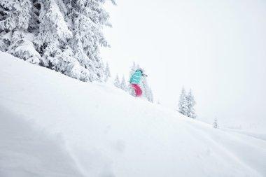 Girl in backcountry snowboarding