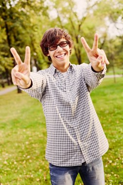 Teenager showing victory sign in park