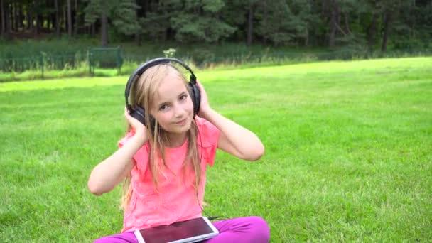 dívka poslouchat hudbu na tabletu venku