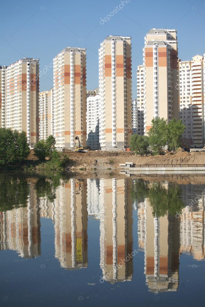 Constructed block of flats over river and clear blue sky in summer day