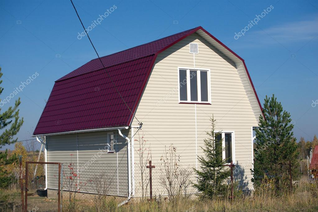 new built country house with red roof and covered with beige siding