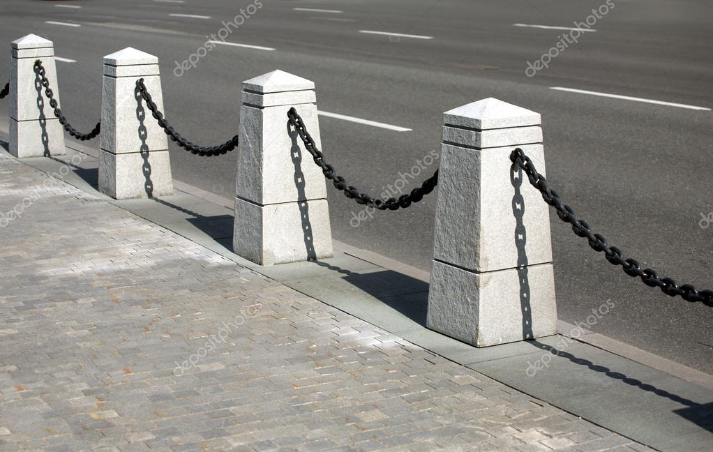Stein-Zaun mit schwarzen Ketten closeup — Stockfoto © iDyMax ...