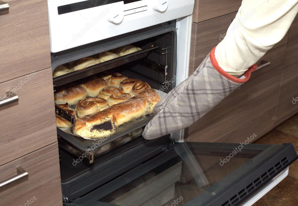open oven in kitchen. hostess open oven door and takes bakery from kitchen stove. side view closeup \u2014 stock in o