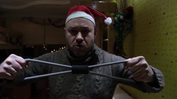 Muž v novoroční čepici ve svetru je zábavné cvičení protahování gumy. Plány zapojit se do tělesné výchovy od nového roku, zdravý životní styl.
