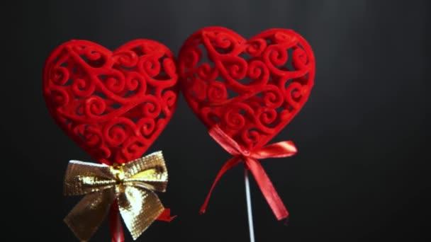 Valentýn. Dvě červené objemové srdce na klacku se objeví na černém pozadí.