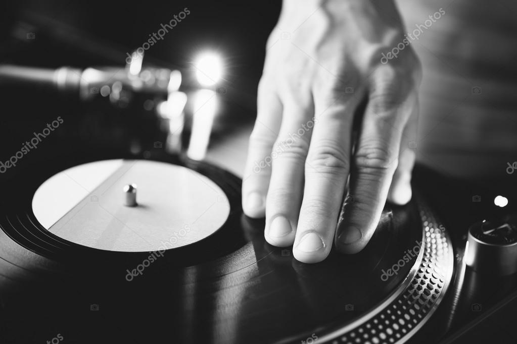 De krabben hand draaitafel van de dj op de vinyl record zwart
