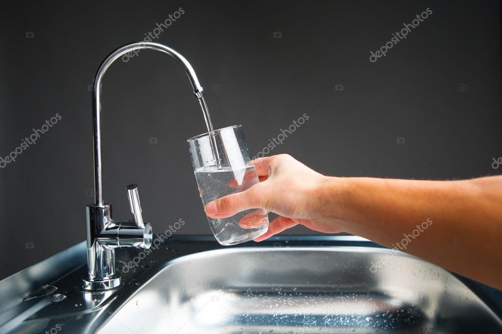 Mano che versa un bicchiere di acqua dal filtro rubinetto u2014 foto