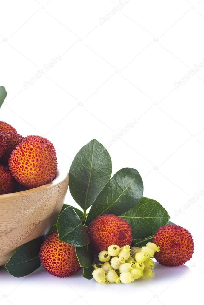 Wooden bowl with arbutus unedo fruits