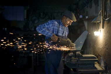 90 years old  blacksmith grinding axe in his workshop