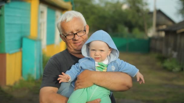 Grandfather holding his grandson in his arms. Beautiful baby smiling