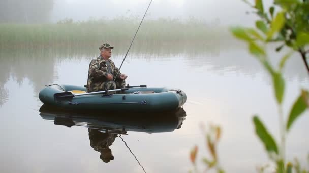 Rybář na lodi hází návnadu. Ranní mlha nad jezerem