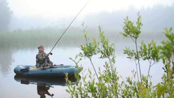 Rybář na lodi lovit. Malé ryby na udici