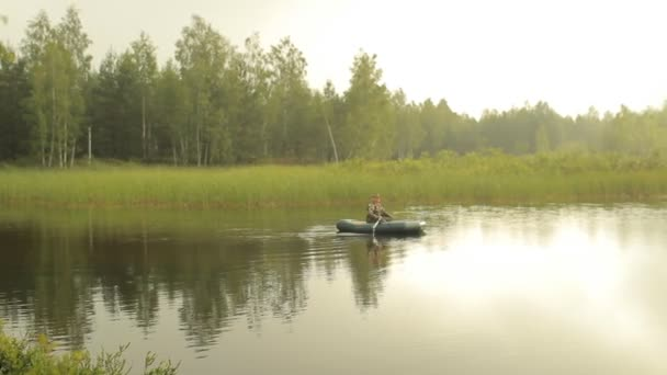 Halász ember úszik a tó egy felfújható csónakot. Kora reggel