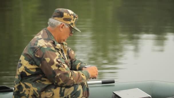 Člověk dotýká chytré hodinky na jezeře. Rybář s rybářským prutem na nafukovací člun