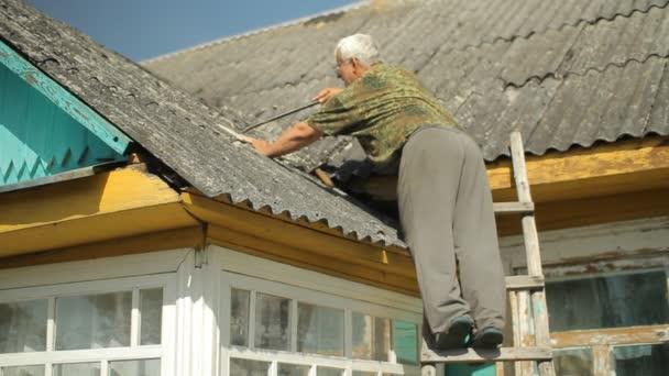 versucht ein Mann, das Dach zu reparieren. er steht auf der Treppe neben dem Haus