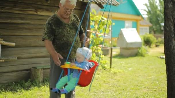 Baby Schommel Tuin.Senior Man Rolt De Mooie Baby Op Een Schommel Grootvader Met Zijn