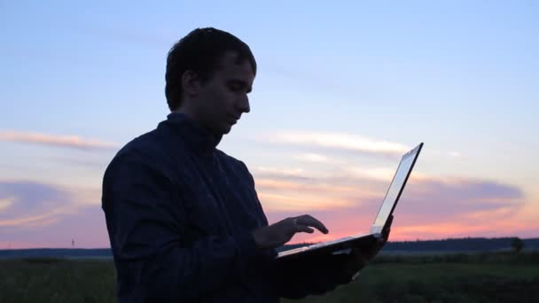 Young man is relaxing outdoors with laptop computer in his hands