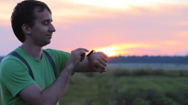 Man touching smart clock on the background of beautiful sunset sky