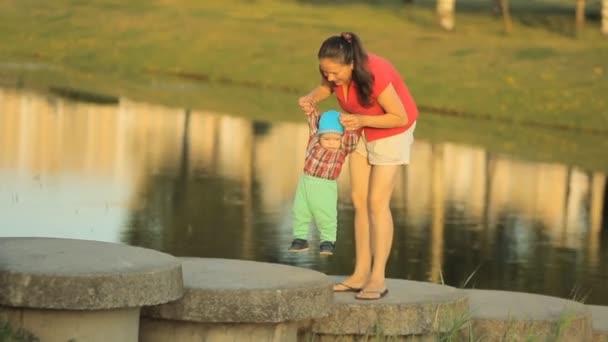 Šťastné matky a syna na cestě v přírodním parku, řeka na slunečný den. Žena, malý chlapeček, dítě, dítě na dovolené. Nádherná příroda. Rodina tráví společně čas venku