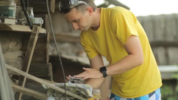 Mladý muž ždímá kovová část ve svěráku. Na pozadí země bytové výstavby