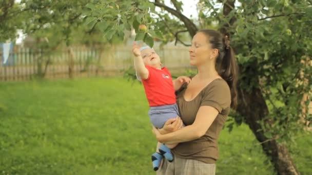 Piccolo neonato con il suo gioco di giovane madre con di melo
