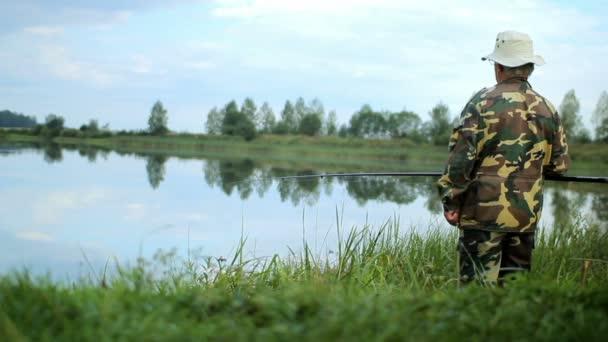 Fisher muž s rybářský prut chytat ryby na jezeře