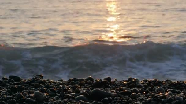Krajina s oranžová obloha při západu slunce. Vlny bila Skalnatá pláž