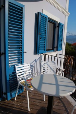 Beautiful terrace or balcony with small table, chairs and blue  jalousies