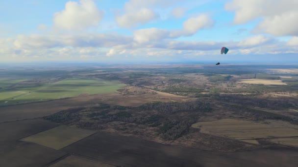 Gleitschirmflügel in großer Höhe über bestellten Feldern