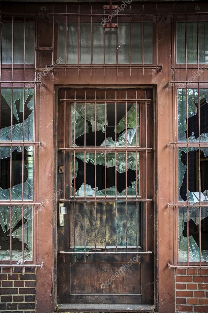 Broken window panes on a barred door u2014 Photo by chrissi & broken window panes on a barred door u2014 Stock Photo © chrissi #101693582