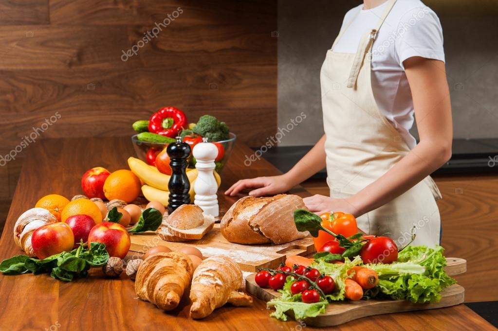 Hausfrau in der Küche in der Nähe von Tisch voll mit Essen ...