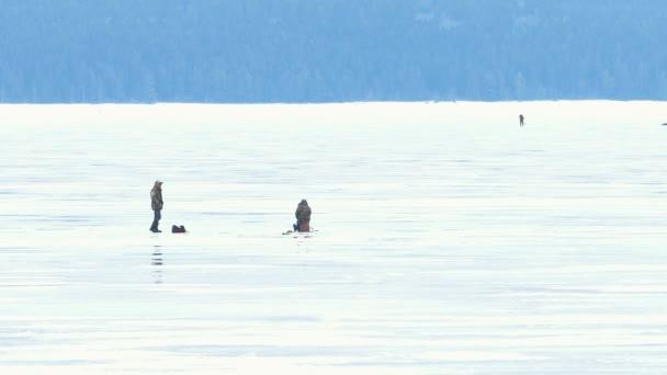 Rybáři na ledu na zamrzlé jezero v zimě