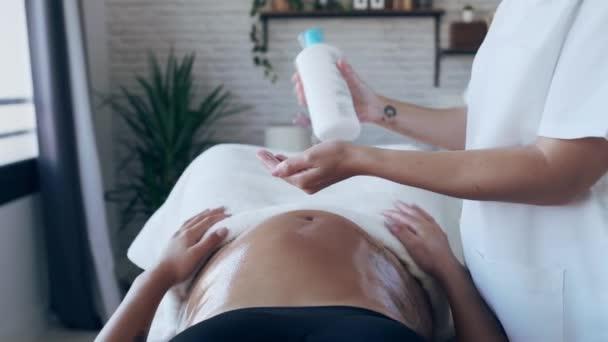 Videó közelről fiatal fizioterapeuta nő masszírozó has terhes nő egy hordágyon otthon.
