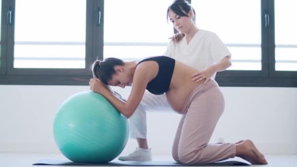 Video der schönen jungen Physiotherapeutin, die der schönen schwangeren Frau hilft, Pilates-Übungen mit Ball zu machen und sich auf die Geburt zu Hause vorzubereiten.