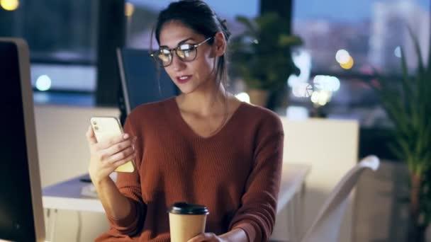 Lövés gyönyörű fiatal üzletasszony, amelynek videojáték mobiltelefon, miközben dolgozik a számítógép ül az irodában.