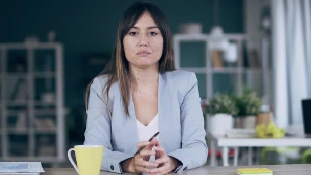 Videó magabiztos üzletasszony keres és beszél a webkamera, miközben egy videokonferencia coworking helyen.