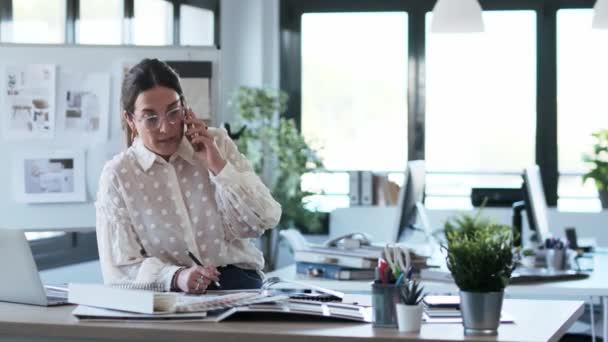 Video einer smarten jungen Designerin, die in einem Designprojekt arbeitet, während sie im Büro mit ihrem Smartphone spricht.