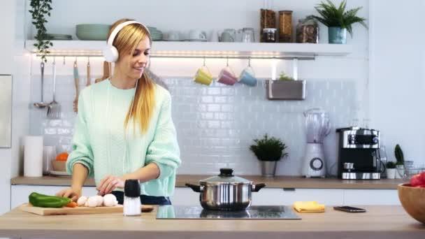Video šťastné krásné ženy vaření zdravé jídlo v kastrolu při foukání lžíce ochutnat jídlo v kuchyni doma.