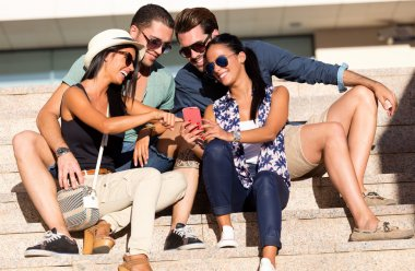 Portrait of group of friends having fun with smartphones.
