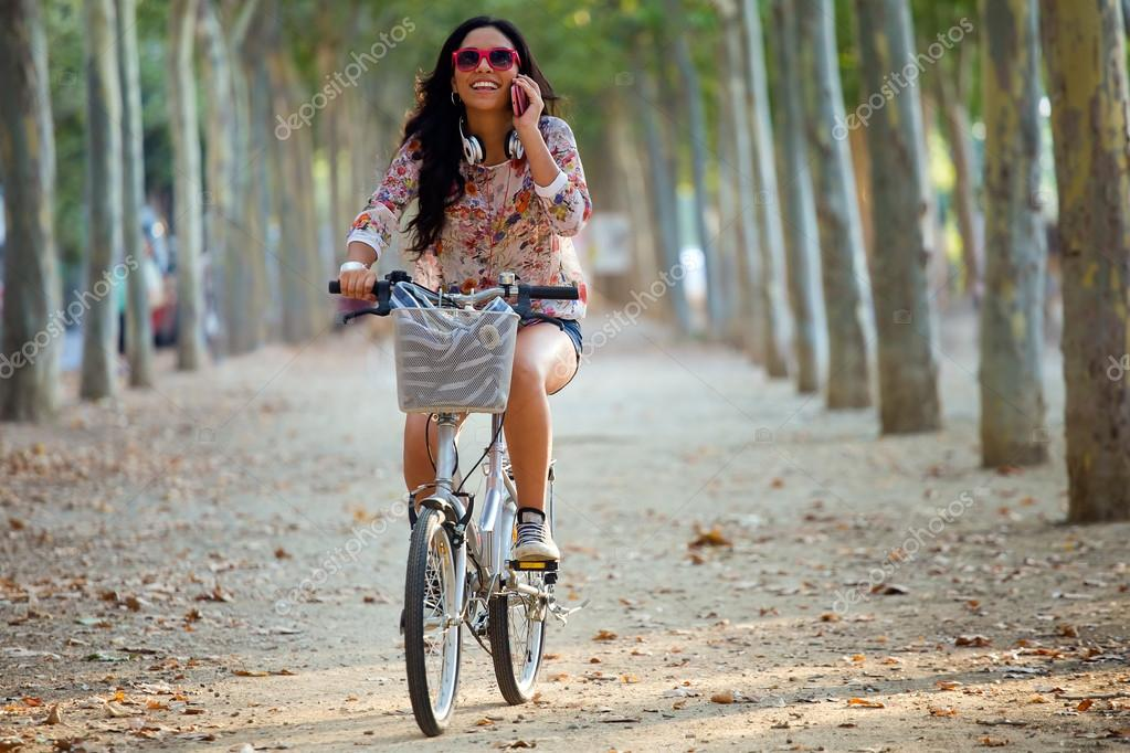 Pretty young girl riding bike and talking on the phone.