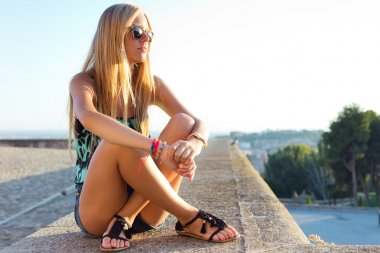Pretty blonde girl sitting on the roof.