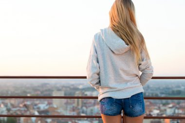 Beautiful blonde stands on the edge of the roof.