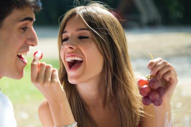 Young couple eating grapes on romantic picnic in countryside.