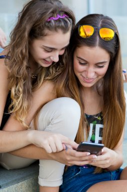 Two students having fun with smartphones after class.