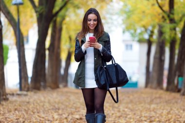 Beautiful girl walking with mobile phone in autumn.