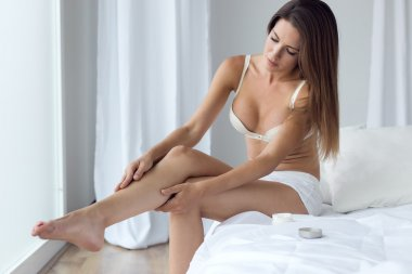 Pretty young woman applying body cream on legs.
