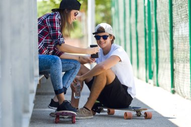 Two skaters using mobile phone in the street.